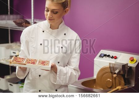 Worker holding chocolate mould in kitchen