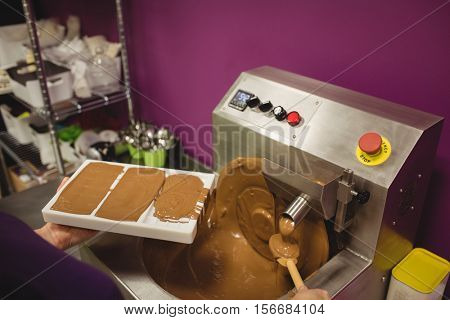 Worker filling mould with melted chocolate in kitchen