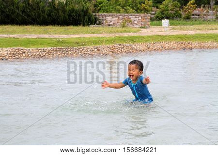 Japanese boy playing with water (1 year old)