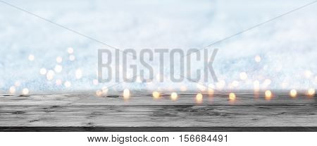 Wintery panorama with lights in front of an empty wooden table for a concept