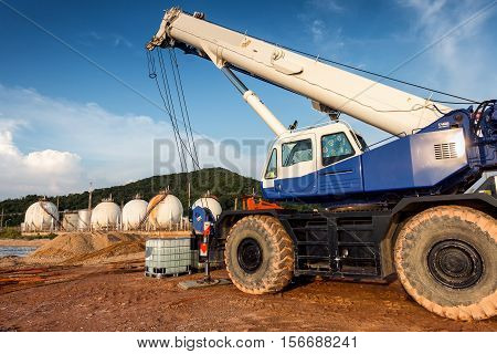 Mobile crane lifting on petrochemical plant background.