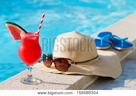 Fresh glass of water-melon smoothie drink with sunglasses, straw hat and slippers on border of a swimming pool - holiday tropical concept