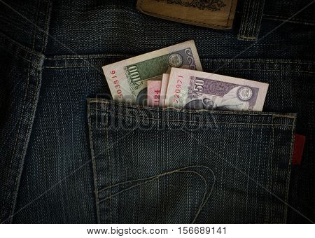Small denomination Indian currency notes stuffed in the back pocket of jeans.
