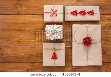 Lots of Gift boxes on wood background. Presents in craft paper decorated with red ribbon bows, fir tree and snowflakes. Christmas and winter holidays parcel concept. Top view, flat lay with copy space