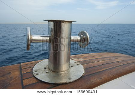 Metal steel capstan post on side teak deck of a luxury motor yacht sailing on tropical ocean
