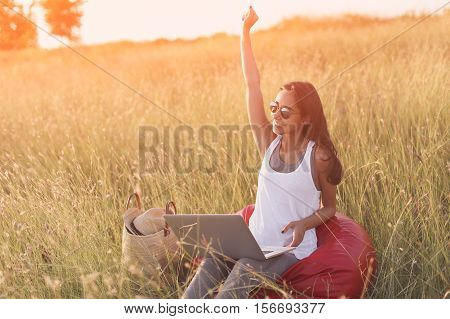 Euphoric woman searching job with a laptop in a meadow. Working at computer outdoors in nature. Happy girl with 4g internet connection