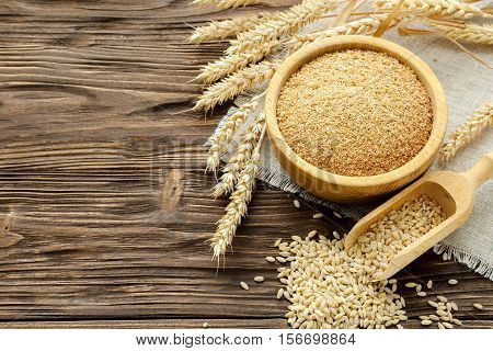 Bran grain and wheat ears on a brown wooden table