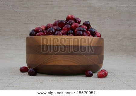 Fresh red and maroon cranberries heaped in a turned wooden bowl with several loose berries. Photographed close up at eye level against an ecru woven cloth background with shallow depth of field and fill flash.