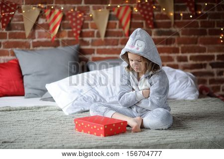 The little girl in a pajamas sits on a big bed and angrily looks at a bright box. The child isn't happy. The girl is disappointed by the received gift. Offense. Protest.