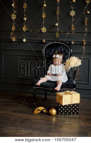 Little girl sits in chair and with enthusiasm looks at smartphone screen. With a wreath on head and barefoot baby is similar to an angel. Room is festively decorated. On a floor boxes with gifts lie.