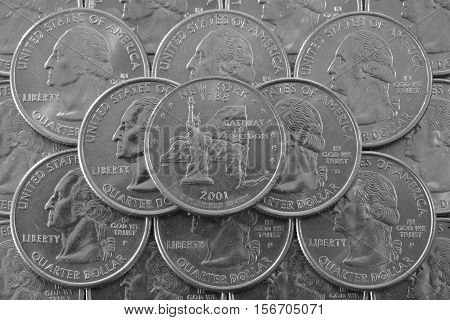 Coins of USA. Pile of the US quarter coins with George Washington and on the top a quarter of New York State.