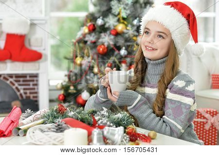 Portrait of cute long-haired girl in Santa hat holding cup of tea looking at the distance
