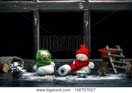 Handmade toy snowman and snowgirl of yarn skeins making beads of pearls over black background. Color toning