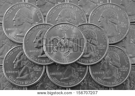 Coins of USA. Pile of the US quarter coins with George Washington and on the top a quarter of Delaware State.