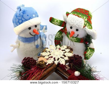 Snowman duo with a snow star and two tassels on white background
