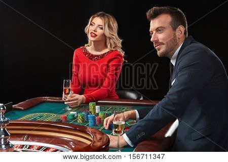 Couple playing roulette wins at the casino. Addiction to the gambling