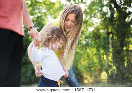 Cute little boy with his beautiful mother and unrecognizable father in green sunny summer nature.