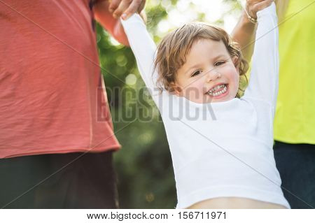 Cute little boy with his unrecognizable father and mother outside in green sunny summer nature.