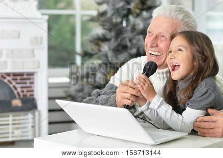 Happy grandfather and his granddaughter singing karaoke at home