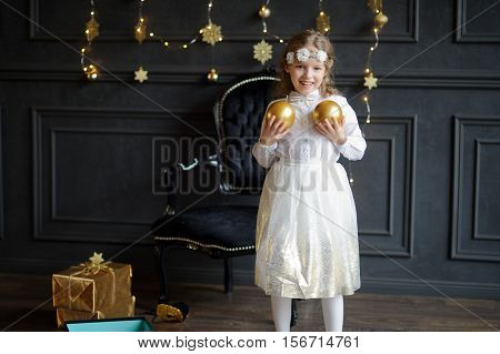 Elegantly dressed girl of 8-9 years plays Christmas-tree decorations. Dark wall is decorated with Christmas garlands. On floor boxes with gifts lie. Cheerful girl holds gold Christmas balls in hand.