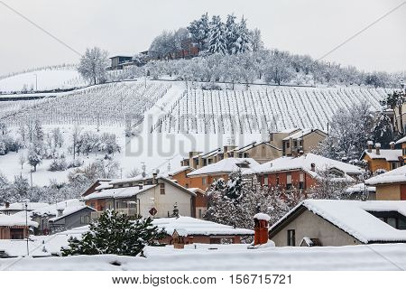 Rural houses on the hill covered with snow in Piedmont, Northern Italy.