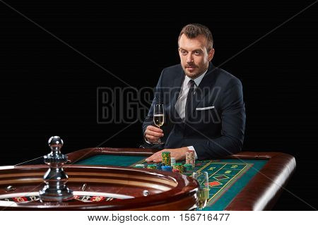 man in a suit playing roulette. addiction to gambling. In the hands of a glass. tensely watching, waiting for the result