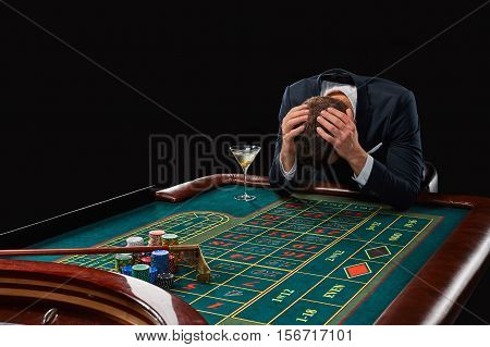 man in a suit playing roulette. addiction to gambling. In the hands of a glass. upset losing