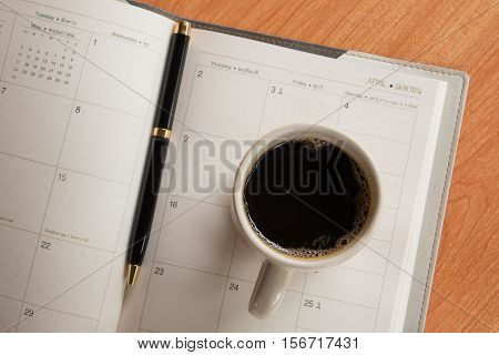 Cup of coffee and pen on notebook with calendar planner on wooden desk background, top view