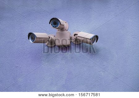 Three security camera on the blue wall