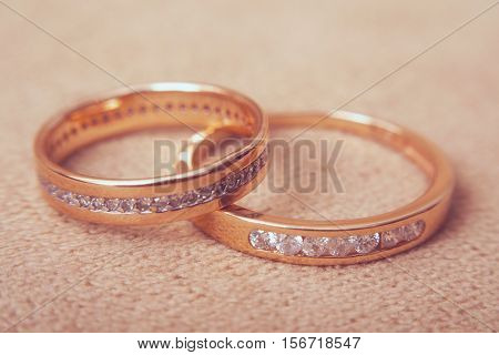Two beautiful golden wedding rings with brilliants close up, vintage toned. Marriage concept