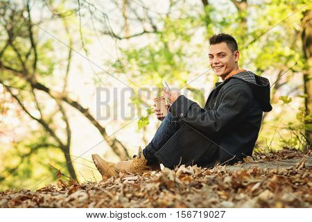 Happy young man in autumn in park with smart phone and takeaway coffee, sitting, smiling. Handsome guy in fall outfit relaxing. No retouch, natural light.