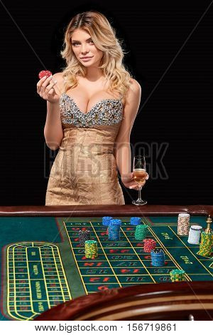 woman in a smart dress plays roulette. addiction to gambling. holding in the hands of chips