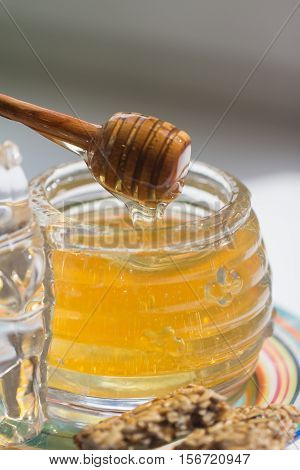 honey dripping From  spoon  into a glass jar