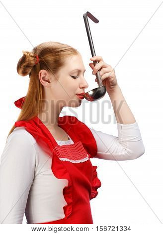 Young beautiful attractive housewife in bright red apron with funny ponytails tasting meal from metal ladle isolated on white background.