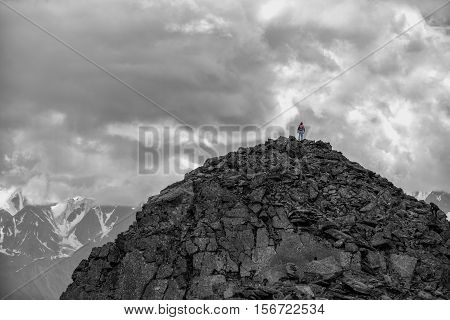 Silhouette of a girl with a backpack on a huge mountain. Very far. Epic black-and-white photo. Altay, Russia.