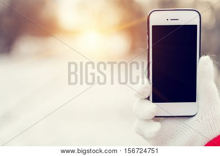 a girl gets on the hip a mobile telephone on a background a winter street