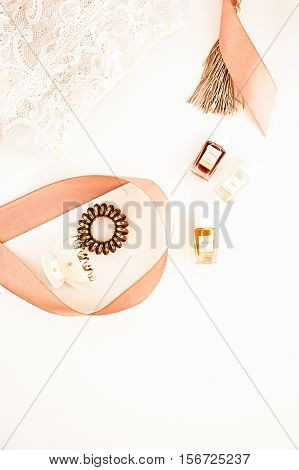 Flat lay for fashion blog and social media. Woman's golden glamour beauty accessories on a white background. Lingerie jewelry perfumes spiral hair ties and hair clips. Copy space for text