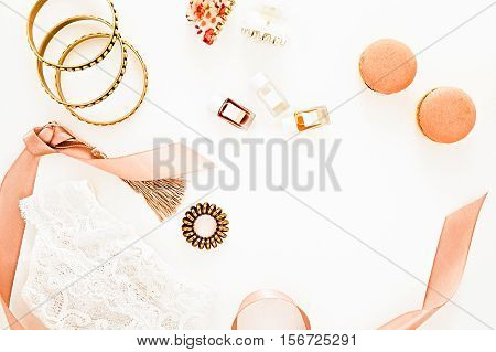 Flat lay for fashion blog and social media. Woman's glamour golden beauty accessories on a white background. Lingerie jewelry perfumes macaroons spiral hair ties and hair clips. Copy space for text. Horizontal