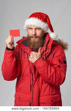 Bearded man in red winter jacket and christmas hat showing blank credit card and gesturing thumb up, over grey background