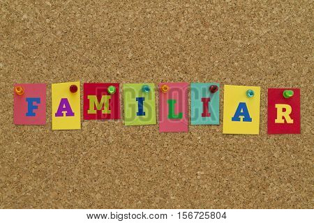 Familiar word written on colorful sticky notes pinned on cork board.