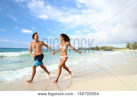Beach summer vacation couple running on holidays. Happy fun beach vacations couple walking together laughing having fun on travel destination. Playful interracial couple in swimwear holding hands. poster