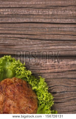 Delicious baked cutlet over wooden surface with copy space for your text. Focus on the cutlet