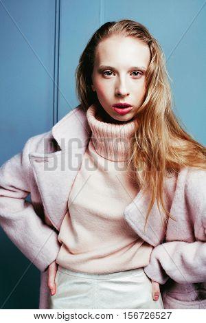 young blonde teenage girl in fur coat, fashion dressed model, studio shot modern hipster