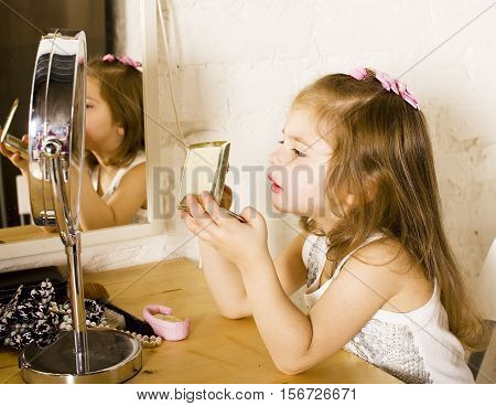 little cute girl with lipstick at mirror, trying do makeup like adult, lifestyle people concept close up