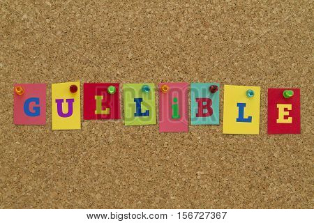 Gullible word written on colorful sticky notes pinned on cork board.