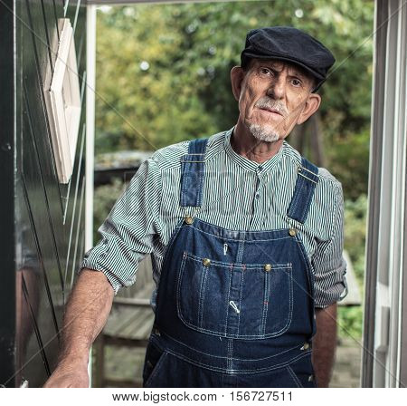 Vintage Senior Farmer Wearing Dungarees And Cap Entering Front Door Of Farm.