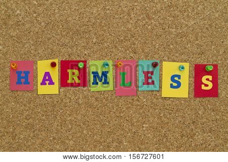 Harmless word written on colorful sticky notes pinned on cork board.
