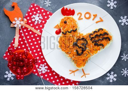 Festive salad shaped rooster or symbol of New Year 2017 on the Chinese calendar. Symbolic food at holiday dinner