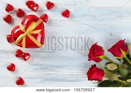 Red roses and heart shaped chocolate candies on rustic wooden table.