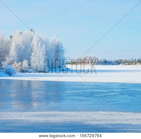 Winter landscape with frozen river and forest in the frost